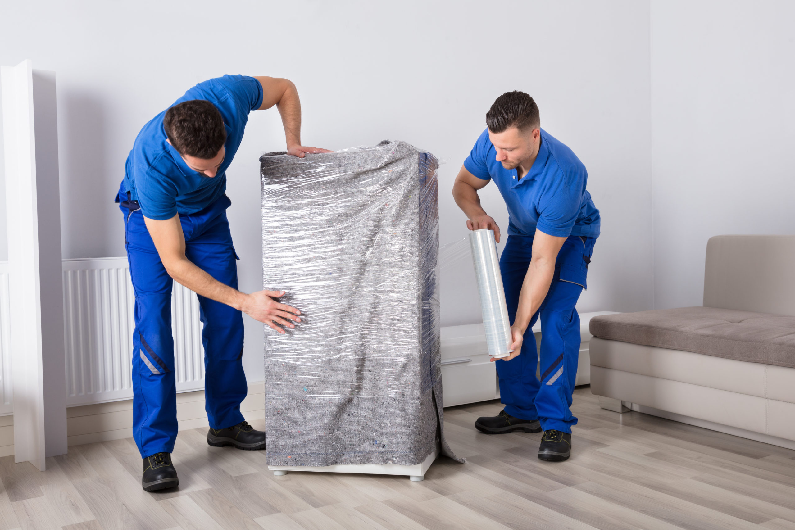 wo Young Male Movers Packing Furniture In Living Room